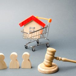 Property auction scene with wooden figures, shopping trolley and judges hammer
