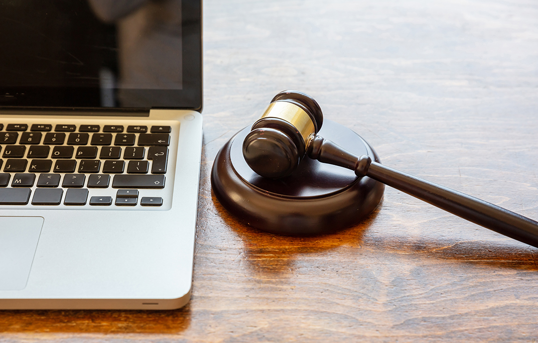 Laptop with an auction judge's hammer beside it