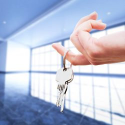 Woman's hand holding keys to an apartment